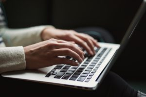 Two female hands typing on a MacBook laptop