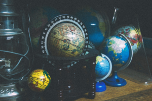 a number of different types of globes sitting on a desk.
