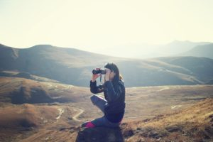 a woman crouching on a mountain looking into binoculars